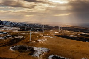wind energy turbines in field with mountains and snow